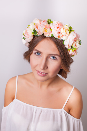 Portrait of a beautiful girl with flowers on her head on a white background.
