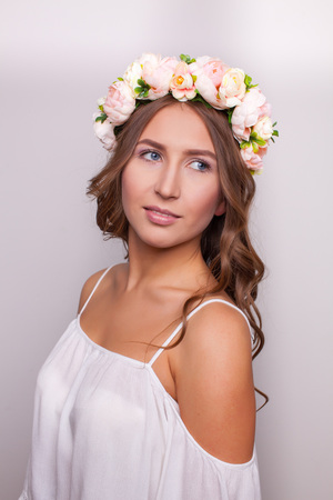 Beautiful girl with vintage flowers on her head on a white background close-up.