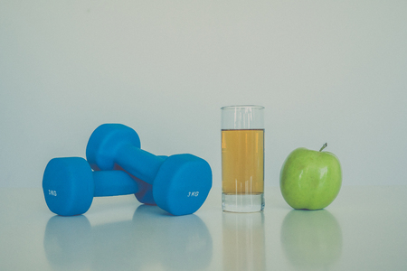 signo pesos: healthy eating concept. Small dumbbells. Apple juice. Green apple on a white background. healthy lifestyle. sport.