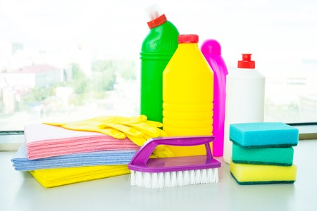 Range of cleaning products for the home. Detergents, chemical bottles, cleaning sponges and gloves. On the background of the window. Stock Photo