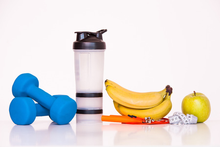 signo pesos: The concept of a healthy diet. Fintes meals. Sport lifestyle. Dumbbells. green apple. Bananas. shaker. The skipping rope. Measuring tape waist. on a white background