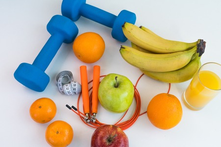 healthy eating concept. Dumbbells, skipping rope, bananas, oranges, measuring tape waist, oranges, red apple, green apple, orange juice on a white table. Fitness diet. view from above 版權商用圖片