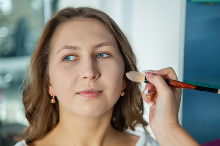 Make up artist doing professional makeup of young woman Stock Photo