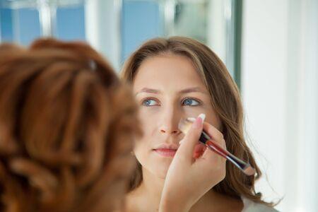hair do: Make-up artist applying bright base color eyeshadow on models eye , close up