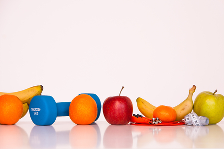 The concept of a healthy diet. Small dumbbells. Bananas. Apples. Oranges. The skipping rope. Measuring tape waist. on a white background. healthy lifestyle. sport. Fitness food. Stock Photo