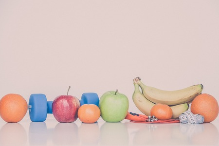 The concept of a healthy diet. Small dumbbells. Bananas. Apples. Oranges. The skipping rope. Measuring tape waist. on a white background. healthy lifestyle. sport. Fitness food. 版權商用圖片