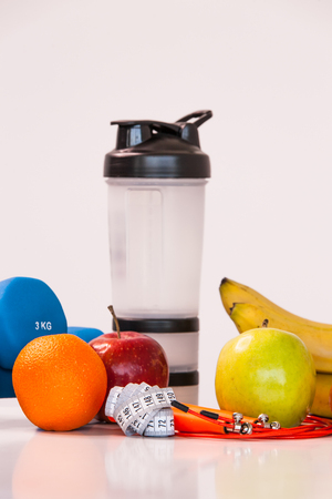 The concept of a healthy diet. Small dumbbells. Shaker. Bananas. Apples. Oranges. The skipping rope. Measuring tape waist. on a white background. healthy lifestyle. sport. Fitness food. close-up