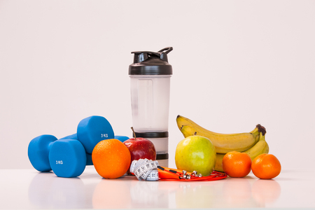 The concept of a healthy diet. Small dumbbells. Shaker. Bananas. Apples. Oranges. The skipping rope. Measuring tape waist. on a white background. healthy lifestyle. sport. Fitness food. 版權商用圖片