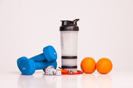 The concept of a healthy diet. Small dumbbells. Shaker. Oranges. Measuring tape waist. The skipping rope. on a white background. healthy lifestyle. sport. Fitness food. 版權商用圖片
