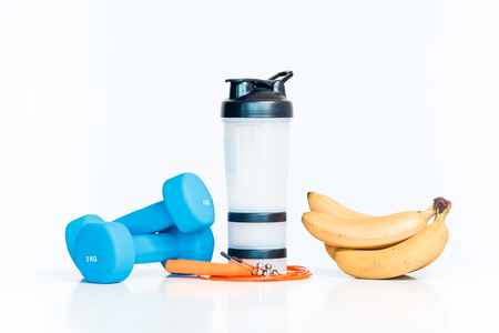The concept of a healthy diet. Small dumbbells. Shaker. Bananas. Measuring tape waist. The skipping rope. on a white background. healthy lifestyle. sport. Fitness food.