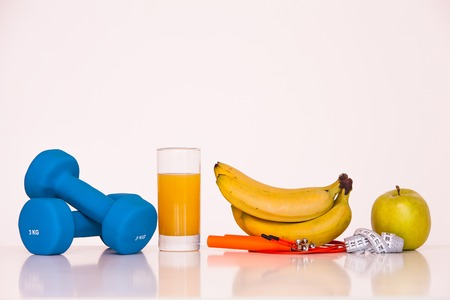 The concept of a healthy diet. Small dumbbells. Orange juice. Bananas. Apples. The skipping rope. Measuring tape waist. on a white background. healthy lifestyle. sport. Fitness food. 版權商用圖片