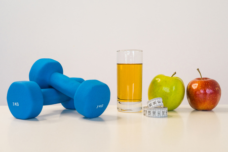 The concept of a healthy diet. Small dumbbells. Apple juice. Measuring tape waist. Green apple. Red Apple. on a white background. healthy lifestyle. sport. Fitness food. 版權商用圖片
