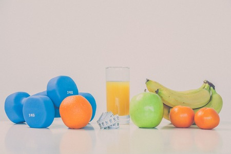 The concept of a healthy diet. Small dumbbells. Orange juice. Bananas. Oranges. Apples. Measuring tape waist. On a white background. healthy lifestyle. sport. Fitness food