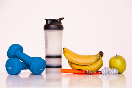The concept of a healthy diet. Small dumbbells. Shaker. Bananas. Apples. The skipping rope. Measuring tape waist. on a white background. healthy lifestyle. sport. Fitness food.