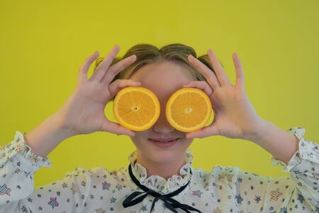 Portrait of a charming young girl in shirt amusing closes his eyes oranges and smiling at the camera