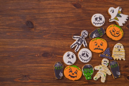 Sweet snacks on the table in the form of ghosts, zombies, pumpkin smileys and coffins. Preparing for a Halloween party Stock Photo