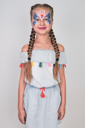 Beautiful little girl with aqua make-up on a white background. face painting