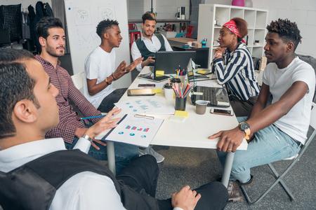 Młodzi obiecujący faceci omawiają innowacyjne projekty w biurze.