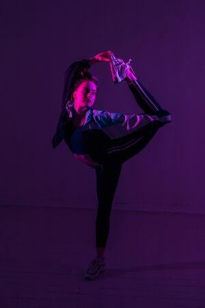 Sporty flexible girl holds her leg over her head in colored light.