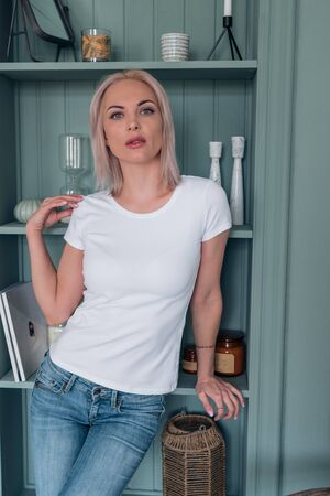 Attractive blonde with short hair in a white t-shirt and jeans looks straight at the camera