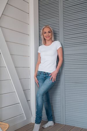 Full-length portrait of an attractive young girl in blue jeans and a clean white t-shirt to create a design or logo