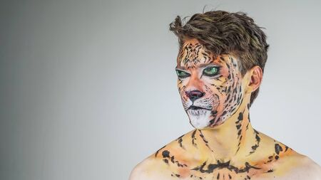 Portrait of a guy painted like a tiger on a gray background. face coloring