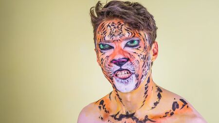 The guy with the painted face of a tiger on a bright background Stock Photo
