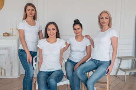 A group of beautiful girls in white t-shirts pose looking straight at the camera. Casual clothing style. 版權商用圖片
