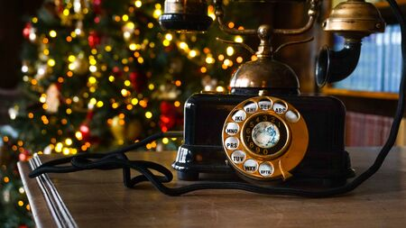 Retro phone close up and Christmas tree in the background