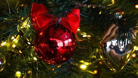 Close - up of a shiny red ball on the Christmas tree. The decoration of the holiday tree. Background