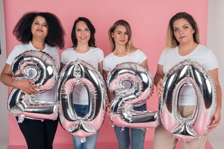 Group of beautiful young girls are holding balloons in the form of figures 2020 next year 版權商用圖片
