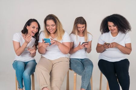 Two girls watch a video on the phone and laugh while two girls look into their phones sitting on a white background
