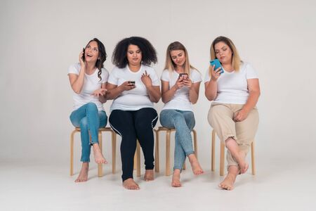 A funny girl is chatting on the phone and three girls are chatting on social media while sitting on chairs in the Studio. Internet and modern man