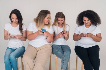 Four young girls use social networks in phones, sitting on chairs on a white background.