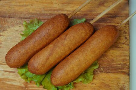 Traditional American food corn dogs on a lettuce leaf. 版權商用圖片