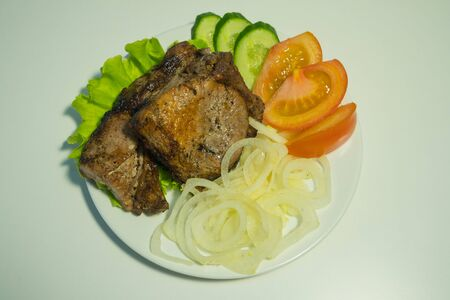 Juicy grilled meat on a white plate with onions, cucumbers and tomatoes and a salad. Zdjęcie Seryjne