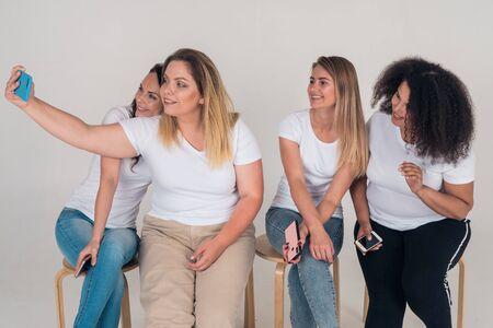 Group selfie girlfriends on mobile phone 版權商用圖片 - 131641854