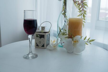 Background. A glass of wine, candles and ornaments on the table by the window