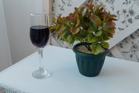A glass of wine and a homemade flower on a table near the wall. Home design. Background