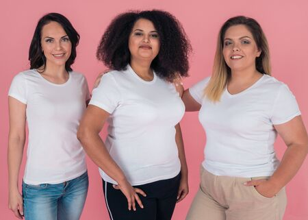 Three girlfriends smile beautifully and pose for the camera on a pink background. Girls in white t-shirts. Layouts for design