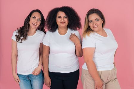 A group of girls in clean white t-shirts on a pink background. T-shirt mock-up for design on clothes 版權商用圖片