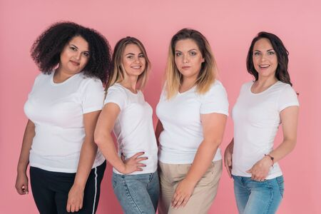 Two plus-size models and two skinny girls in white t-shirts. Design on white womens t-shirts 版權商用圖片