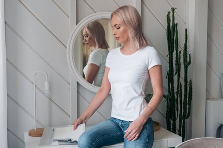 Delicate portrait of a beautiful blonde in a white t-shirt and blue jeans