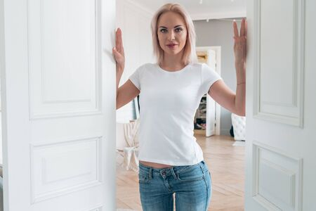 A blonde in a white t-shirt and blue jeans poses for the camera. Layout for design on t-shirt 版權商用圖片