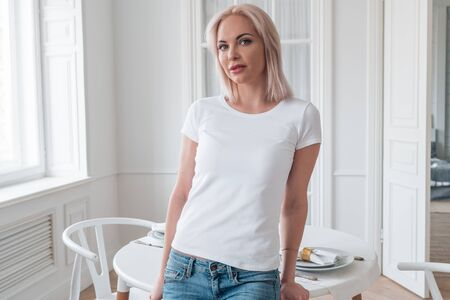 A blonde in a white t-shirt and blue jeans poses for the camera. Layout for design on t-shirt Imagens