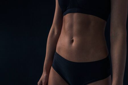 Sports women's abs cubes on the stomach. Thin waist girls. The perfect figure of a woman close-up. 版權商用圖片