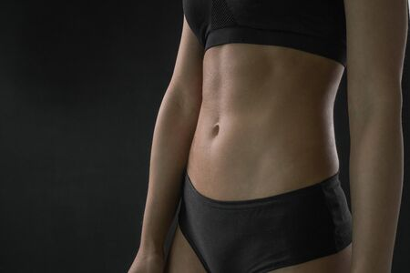 Sports women's abs cubes on the stomach. Thin waist girls. The perfect figure of a woman. 版權商用圖片