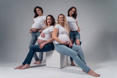 Four pregnant girls in white t-shirts and jeans. 版權商用圖片