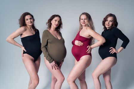 Four pregnant girls in swimsuits on a white background 版權商用圖片