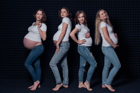 Pregnant women in white shirts and jeans on black background.
